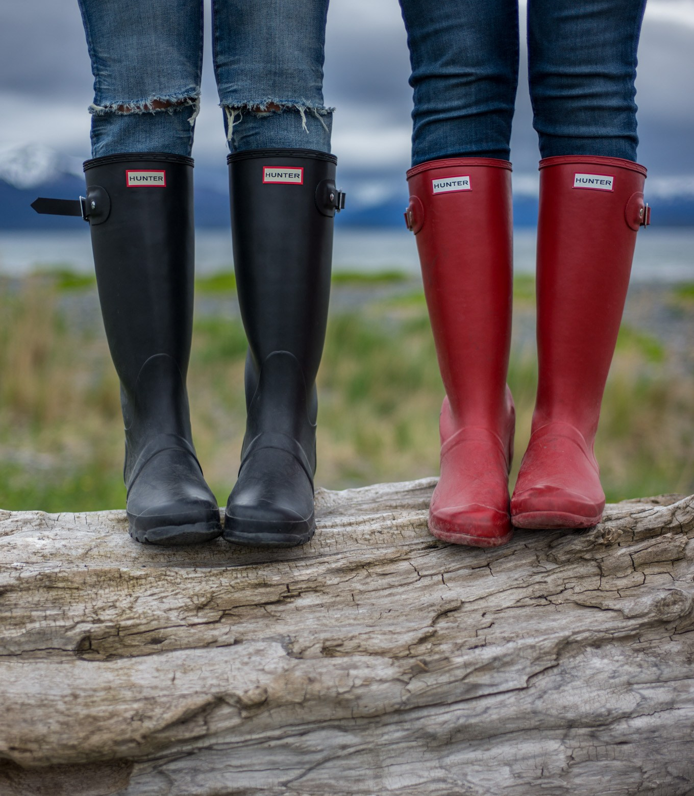 Two gals in Hunter boots on a huge log in the great outdoors.
